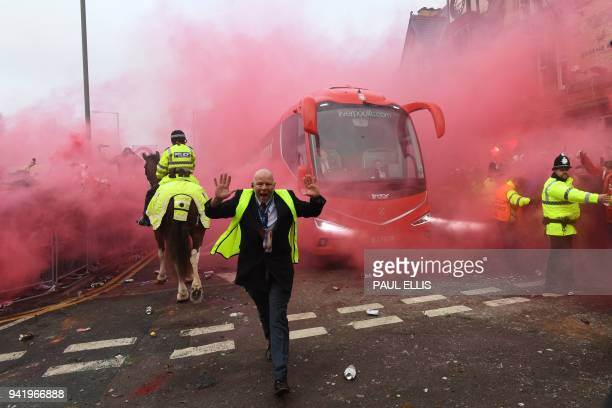 TOPSHOT Police hold back supporters as Liverpool players arrive by bus at the stadium before the UEFA Champions League first leg quarterfinal...