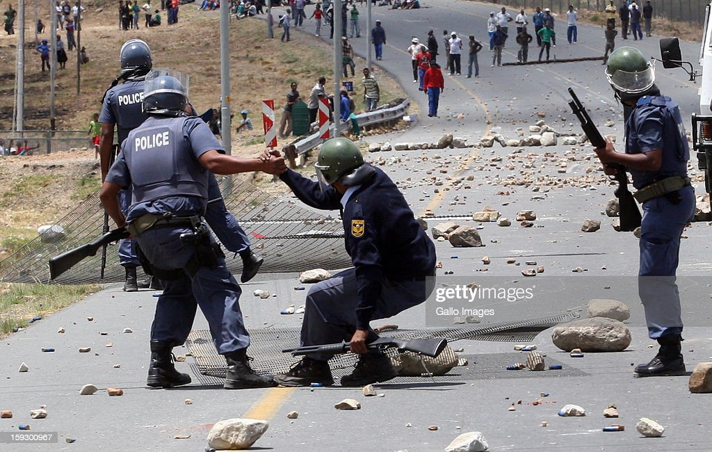 Police hold off striking farm workers as they make barricades to block off the N2 on January 10, 2013 in Grabouw, South Africa. Seasonal farm workers are striking over wage disputes.