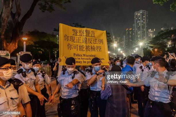 Police hold up a warning banner as they disperse people out of Victoria Park in the Causeway Bay district on June 4, 2021 in Hong Kong, China. The...