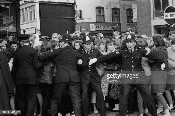 Police holding back crowds of teenagers in a queue for tickets to a Beatles concert on the corner of Halford Street and Charles Street Leicester 20th...