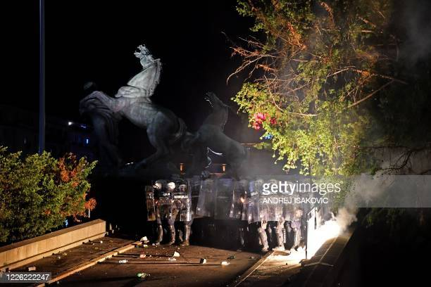 Police holding shields guard the entrance to the National Assembly building in Belgrade, on July 10 during clashes with protesters at a demonstration...