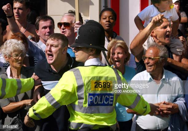Police holds back an angry mob screaming abuse as the convoy carrying suspect Maxine Carr leaves the Peterborough magistrates court some 90 miles...