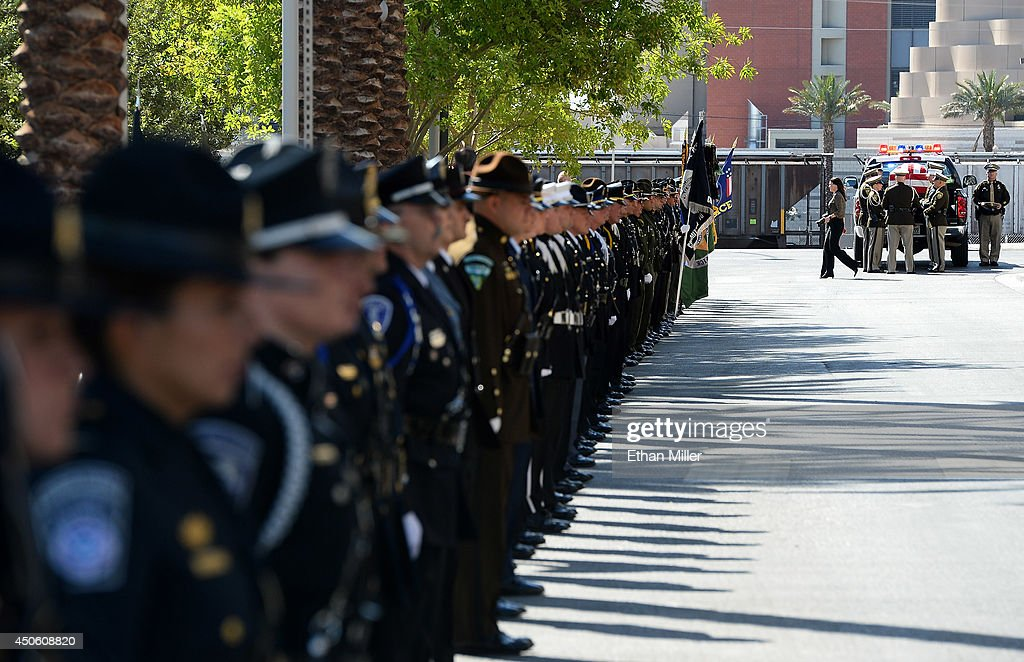 Police honor guard members stand by as officers remove the flag-draped casket of Las Vegas Metropolitan Police Department Officer Alyn Beck from a police vehicle at his funeral at The Smith Center for the Performing Arts on June 14, 2014 in Las Vegas, Nevada. Police said Beck and Officer Igor Soldo were shot and killed on June 8 at a restaurant by Jerad Miller and his wife Amanda Miller. Police said the Millers then went into a nearby Wal-Mart where Amanda Miller killed Joseph Wilcox before police killed Jerad Miller and Amanda Miller killed herself.