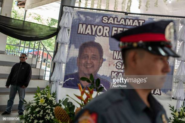 A police honour guard and a private bodyguard stands next to a tarpaulin of General Tinio Mayor Ferdinand Bote who was assassinated by unidentified...