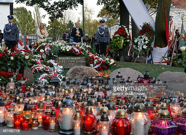 Police honour guard pay tribute by Polish priest Jerzy Popieluszko's grave during ceremonis in front of his parish church in Warsaw on October 19...