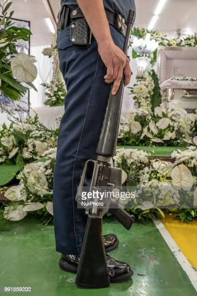 A police honour guard stands next to the remains of General Tinio Mayor Ferdinand Bote who was assassinated by unidentified gunmen on motorcycles...