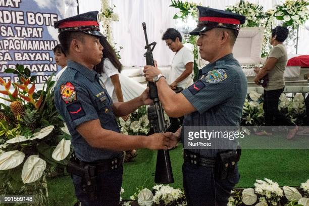 Police honour guards stand next to the remains of General Tinio Mayor Ferdinand Bote who was assassinated by unidentified gunmen on motorcycles...