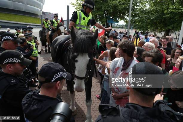 Police horses form a barrier between protestors and the entrance to the Undersea Defence Technology conference organised by the Sink the Arms Fair...