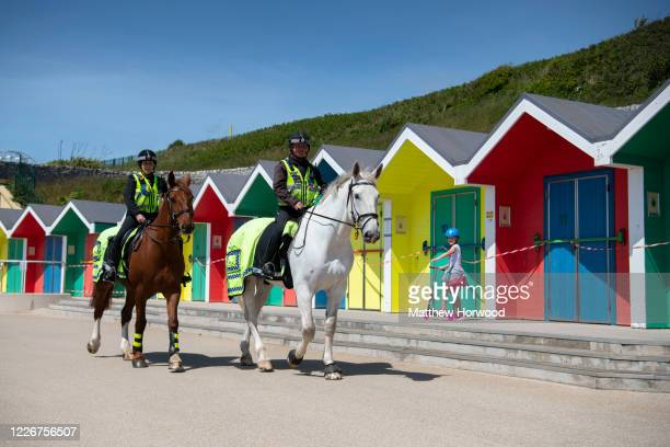Police horses patrol in front of taped off beach huts at Whitmore Bay on May 24 2020 in Barry United Kingdom The British government has started...