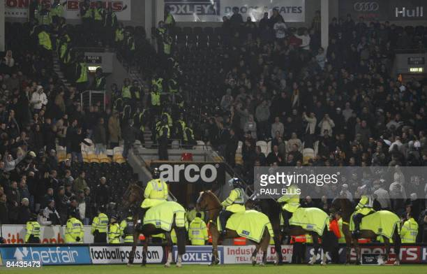 Police horses stand on the pitch as Millwall and Hull City supporters are kept apart after their English FA Cup football match at The Kingston...