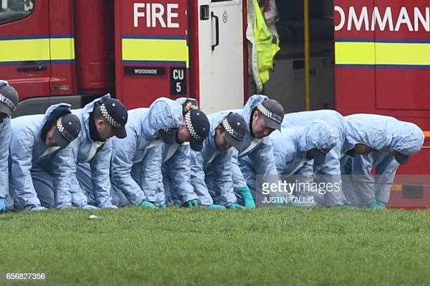 Police in forensic suits search the a grassed area in Parliament Square outside the Houses of Parliament in central London on March 23 2017 the day...