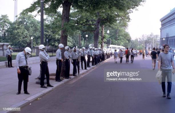 Police in full riot gear stand on the sidewalk as people walk in the street during a Vietnam protest circa May, 1970 in Washington, D.C.