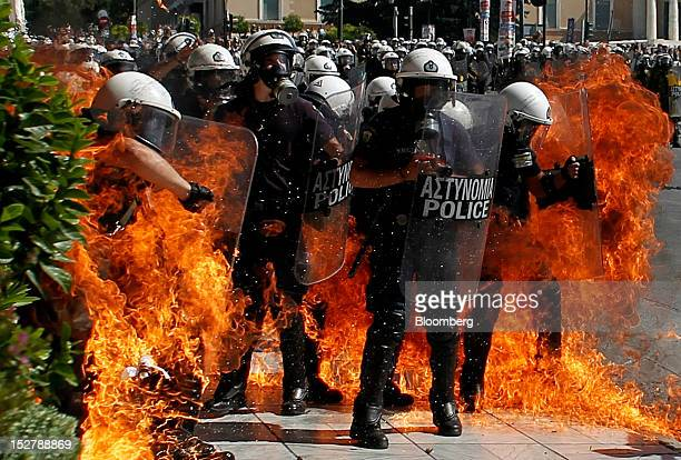 Police in riot gear are caught in the flames from a petrol bomb thrown during demonstrations in Athens Greece on Wednesday Sept 26 2012 Police fired...
