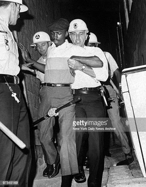 Police in riot gear capture a man suspected of throwing Molotov cocktails during racial riots in the city