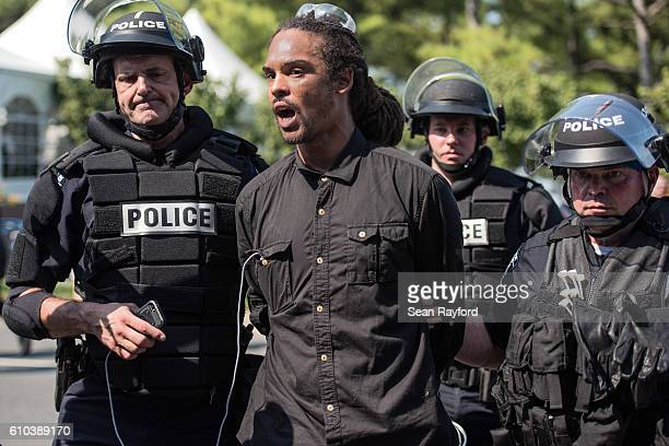 Police in riot gear detain a demonstrator outside of Bank of America Stadium before an NFL football game between the Charlotte Panthers and the...