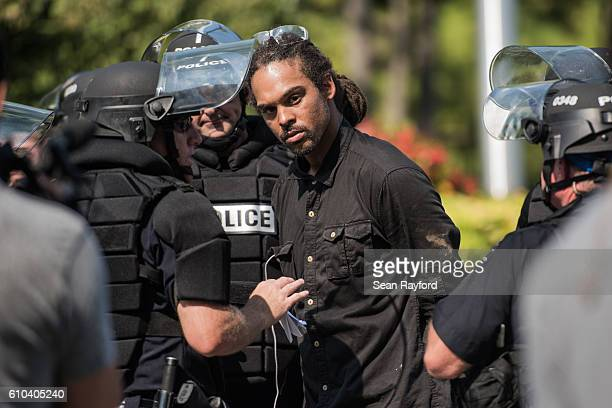 Police in riot gear detain Braxton Winston outside of Bank of America Stadium before an NFL football game between the Charlotte Panthers and the...