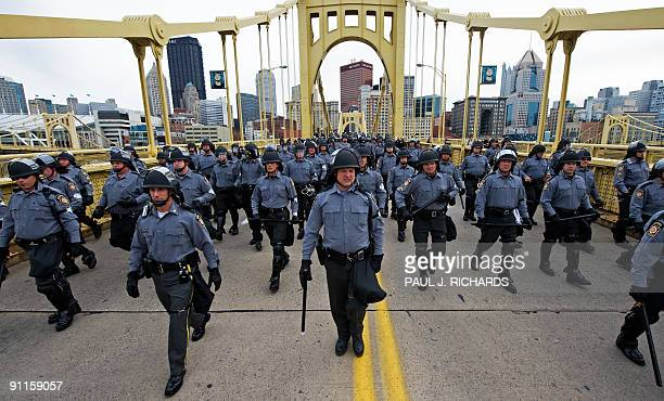 Police in riot gear follow protestors across a bridge in Pittsburgh Pennsylvania as world leaders attend the G20 Summit on September 25 2009 Police...