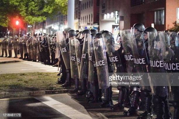 Police in riot gear form a line across Franklin Arterial on Tuesday night.