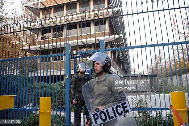 Police in riot gear guard a gate following a break in by protesters at the British Embassy during an anti-British demonstration in the Iranian...