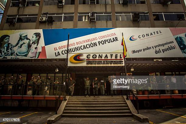 Police in riot gear guard the offices of Conatel the National Telecommunications Commission during a demonstration by a group made up of mostly...