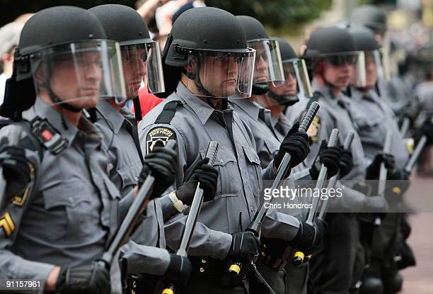 Police in riot gear line the route through downtown Pittsburgh as protesters march by near the site of the G20 summit meeting held on September 25...
