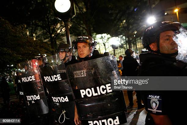 Police in riot gear look on as residents and activists march in the streets amid heavy police and North Carolina National Guard presence to protest...