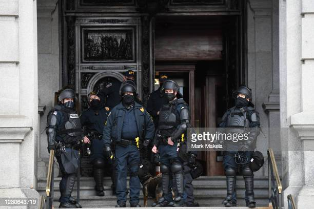 Police in riot gear monitor activity outside the Pennsylvania Capitol Building on January 17, 2021 in Harrisburg, Pennsylvania. Supporters of...