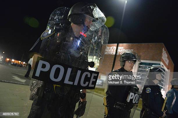 Police in riot gear respond to demonstrators blocking traffic during a protest outside the Ferguson Police Department on March11 2015 in Ferguson MO...