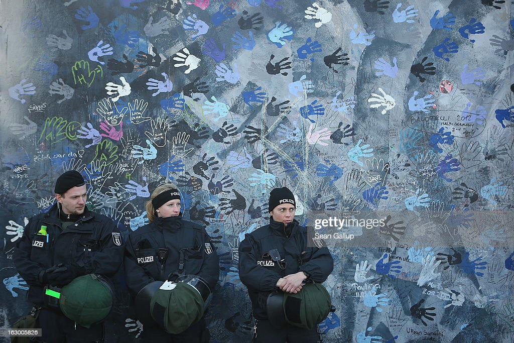 Police in riot gear stand guard at a section of the East Side Gallery, which is the longest still-standing portion of the former Berlin Wall, that is to be removed tomorrow by a construction company building a high-rise luxury apartment block on March 3, 2013 in Berlin, Germany. A real estate developer is planning to build a 14-storey apartment building between the East Side Gallery and the Spree River and needs to remove the Wall section in order to allow access to the construction site. Protesters managed to temporarily halt the dismantling of the section on March 1. Critics, including East Side Gallery mural artists and Spree River embankment development opponents, decry the move, citing the importance of the East Side Gallery's status as a protected landmark and a major tourist attraction. The East Side Gallery is approximately 1.3 kilometers long.