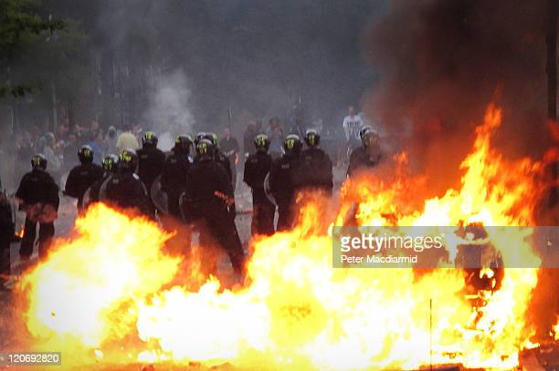 Police in riot gear stand near a burning car as it explodes in Hackney on August 8 2011 in London England Pockets of rioting and looting continues to...