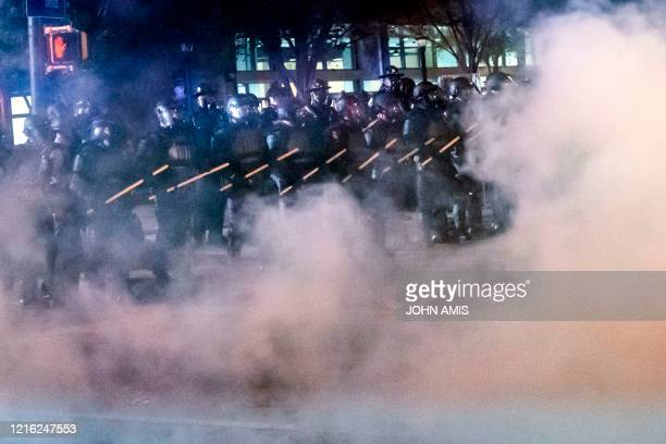Police in riot gear stand near Centennial Olympic Park during rioting and protests in Atlanta on May 29 2020 The death of George Floyd on May 25...