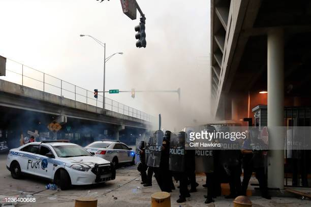 Police in riot gear use tear gas and other means of crowd control as they blockade the station's parking garage as a rally in response to the recent...
