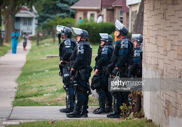 Police in riot gear wait in an alley after a second night of clashes between protestors and police August 15 2016 in Milwaukee Wisconsin Hundreds of...