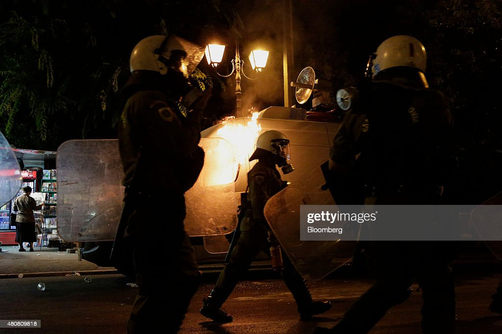 Police in riot gear walk towards protesters during clashes on Syntagma Square in central Athens, Greece, on Wednesday, July 15, 2015. Greek police clashed with protesters in central Athens as lawmakers debated a new bailout of up to 86 billion euros ($94 billion) that will impose further austerity on a country already ravaged by recession. Photographer: Matthew Lloyd/Bloomberg via Getty Images