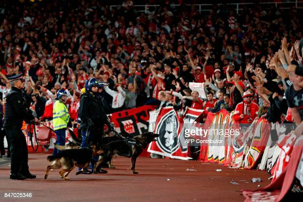 TOPSHOT Police inside the stadium keep an eye on Cologne supporters in the stands as the kick off is delayed due to crowd safety issues ahead of the...