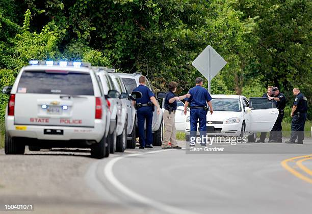 Police insoect a car with bullet holes along LA 3217 after two St John the Baptist sheriff's deputies were killed and at least one other injured in a...