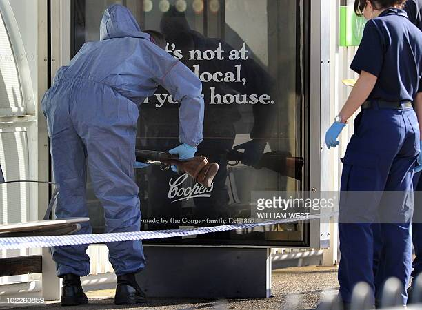 Police inspect a gun abandoned by suspected gunman 19yearold David Paul Rowntree near the Rod Laver tennis centre in Melbourne on June 21 2010 Police...