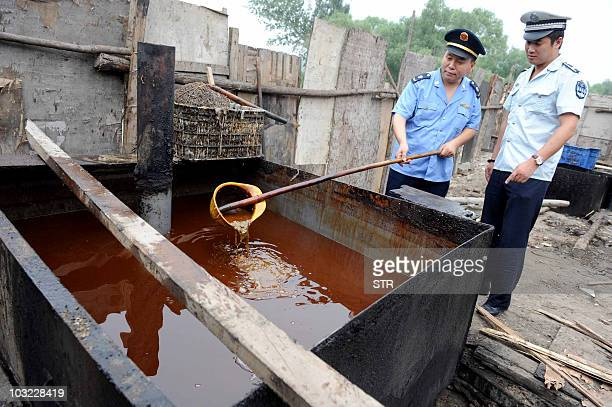 Police inspect illegal cooking oil better known as 'drainage oil' seized during a crackdown in Beijing on August 2 after reports said up to onetenth...