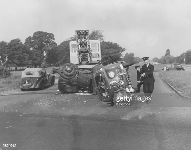 Police inspect overturned cars at the scene of a road accident on the Southend arterial road near Warley