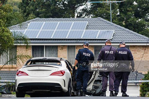 Police inspect the burntout remains of a vehicle used during a shooting at Bankstown Central Shopping Centre on April 29 2016 in Sydney Australia One...