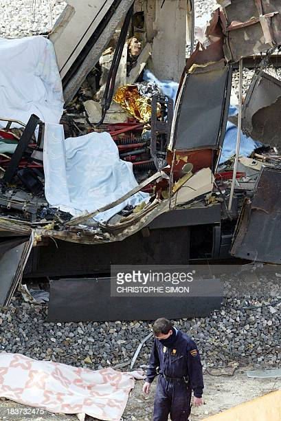 Police inspect the debris after a train exploded near the Atocha train station in Madrid 11 March 2004 At least 131 people were killed and some 400...