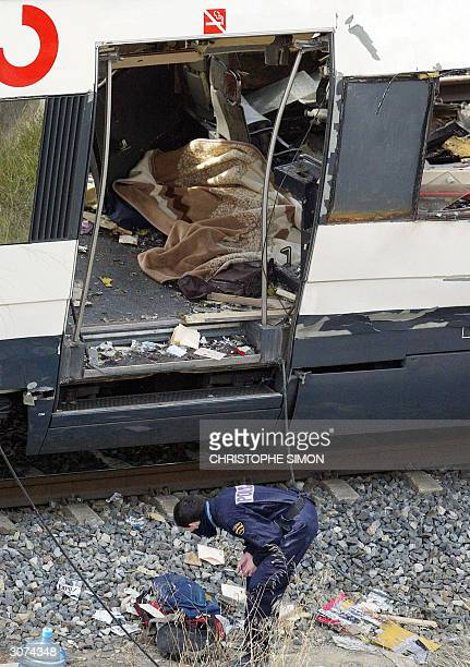 Police inspect the train that exploded near the Atocha train station in Madrid 11 March 2004 At least 131 people were killed and some 400 injured...