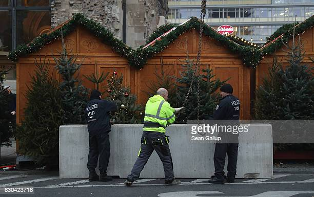 Police install concrete blocks as a security barrier on the periphery of the reopened Breitscheidplatz Christmas market where three days ago a truck...
