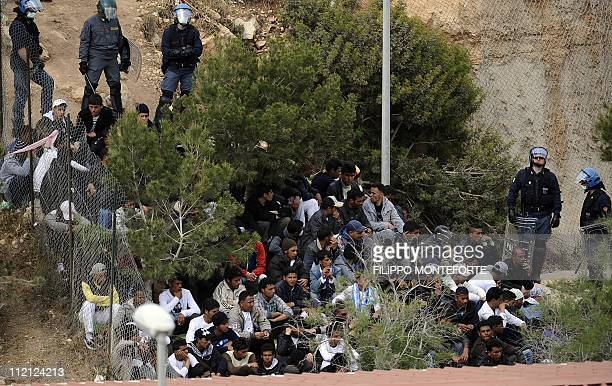 Police intervene to restore order in a temporary staying center on the Italian island of Lampedusa after migrants set fire and tried to escape on...