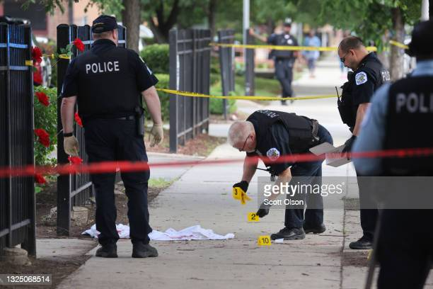 Police investigate a crime scene where three people were shot at the Wentworth Gardens housing complex in the Bridgeport neighborhood on June 23,...