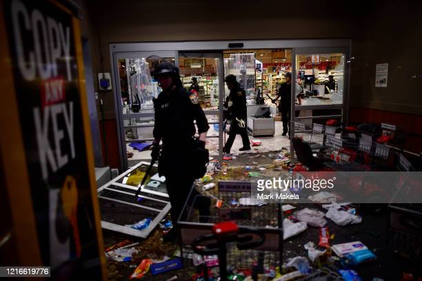 Police investigate a looted grocery store during widespread unrest following the death of George Floyd on May 31 2020 in Philadelphia Pennsylvania...