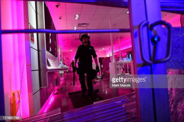 Police investigate a looted T-Mobile store during widespread unrest following the death of George Floyd on May 31, 2020 in Philadelphia,...