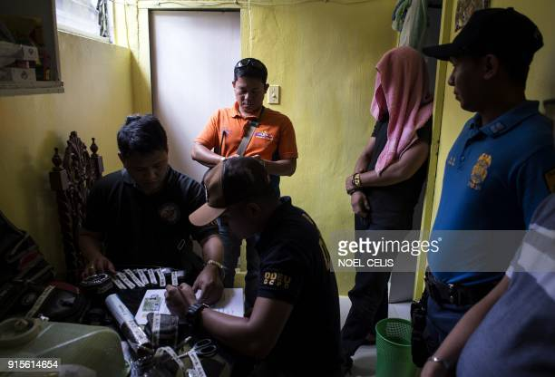 Police investigate drug paraphernalia discovered as a suspect covers his face after a drug raid in Manila on February 8 2018 Philippine President...