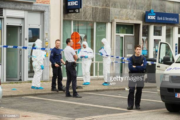 Police investigate on a crime scene in front of a jewellery store in Ledeberg Gent following a robbery on June 21 2013 Two armed robbers attacked a...