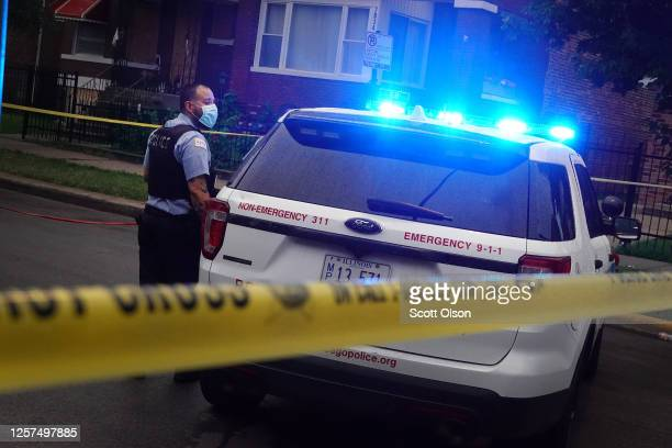 Police investigate the scene of a shooting in the Auburn Gresham neighborhood on July 21 2020 in Chicago Illinois At least 14 people were transported...